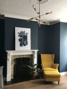 Hague Blue farrow and ball, wood burning stove, yellow ikea armchair, copper pendant lamp. Blue Feature Wall Living Room, Farrow And Ball Living Room, Navy Blue Living Room, Living Room Ideas Dark Blue, Blue And Copper Living Room, Dark Blue Dining Room, Dark Wood Living Room, Ikea Living Room, Living Room Chairs