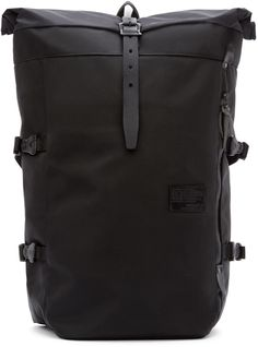 Lightweight and tear-proof textile backpack in black. Adjustable padded textile and leather shoulder straps. Padded back. Concealed zippered storage pockets and compression straps at sides. Logo patch in black at front. Leather strap with pin-buckle closure and foldover flap at main compartment. Lined interior. Tonal stitching. Approx. 17