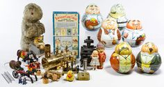 """Lot 685: Toy and Tin Assortment; Including six Bristolware roly poly tin containers, a cast iron """"Queen"""" miniature stove, a brass steam engine, tin friction-driven toys, rubber and plastic dolls, cast iron fire truck parts, a mohair stuffed animal and Schall & Co. birthday party favors"""