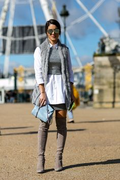 A furry vest, crop top, button-down blouse, thigh-high boots and blue accessories.