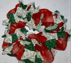Christmas Holly and Deco ! Holly and Christmas  pieces of fabric placed  onto deco mesh. 65 inches around, 6 inches deep. #$65.00 free shipping