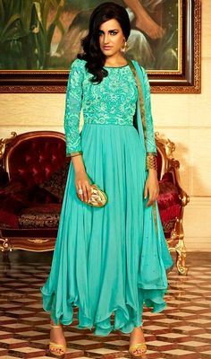 Envelope yourself in a plethora of eternal bliss with this aqua blue color embroidered georgette Anarkali suit. The ethnic lace and resham work over a attire adds a sign of elegance statement with your look. #boatneckanarkalidress #umbrellafrillanarkalisuits #aquabluegeorgetteanarkalisuits