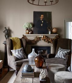 The owner of this Georgia home shopped Stanton Home Furnishings, his own home-goods store, for the living room's corduroy-upholstered wing chairs, fern-print pillows, and antique demijohns. The drum-shaped ottomans are by Lee Industries; the oil portrait dates to the 1860s. The wall is painted Burlap by Ralph Lauren. Bright idea: A bunch of dried magnolia leaves adds up to one lush garland. Get the step-by-step directions to make your own.   - CountryLiving.com