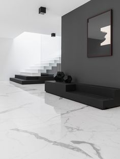 The marble floor contrasts nicely against the solid black wall while unifying the overall colour scheme with its dark veins.