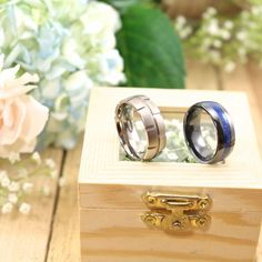 Beautiful blue ceramic wedding band on the right and a carved  titanium wedding band on the left!