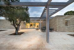 Atmosfera rilassata e tranquilla per la spaziosa veranda lastricata in pietra Chianca di produzione locale della masseria green in Salento. Un progetto ecosostenibile di Massimo Iona Ghini