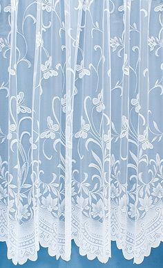 White floral net curtains with a light and airy romantic design.