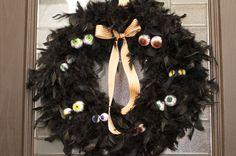 Halloween wreath made with black boas and foam balls coloured to look like creepy eyes |   Inspired by http://pinterest.com/pin/134263632612212280/