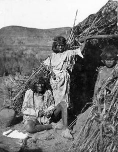man, boy, and girl near a wickiup