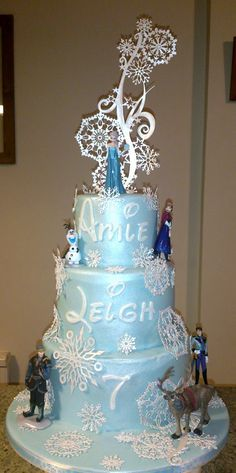 3 tier Frozen inspired cake with snowflake cake lace and figures to finish it off.