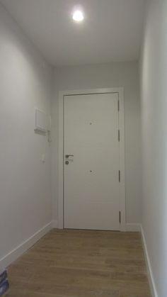 """Detalle de interior de puerta blindada de entrada, lacada en blanco con decoración de 4 franjas horizontales tipo """"pico de gorrión""""."""