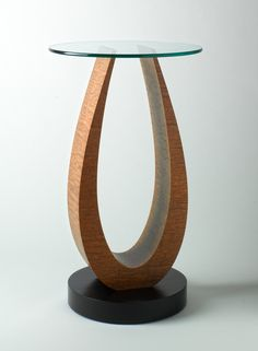 "Tong Pedestal: Using the bent lamination technique, Judd coaxes a birch wood core into an elegant arc, then finishes it with a veneer of either pommele sapele or white ash. The round poplar base has a black varnish. Glass top is 18"" diameter and 3/8"" thick. $1250.00"