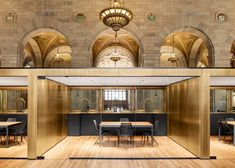 A line of conference rooms is divided by internal partitions and clad in bronze-plated steel to match the ornate detailing of the high ceiling of this renovation by Henri Cleinge.