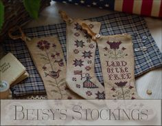 """Betsy's Stockings"" is the title of this cross stitch pattern from Plum Street Samplers that is stitched with Weeks Dye Works Cross Stitch Christmas Stockings, Cross Stitch Stocking, Cross Stitch Art, Cross Stitch Designs, Cross Stitch Patterns, Christmas Cross, Primitive Crafts, Sewing Crafts, Needlework"