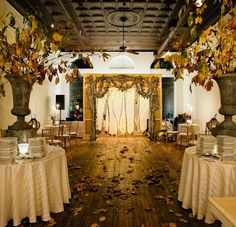 Dramatic autumn wedding décor.  I love the big urns with real branches of leaves and colorful leaves on the floor!