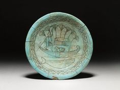 Glazed Dish. Found at Enkomi, Cyprus in a tomb, made in Egypt, 1340-1200 BC    Late Cypriot II    Faience dish; Egyptian or Egyptianising decoration. Decorated in black paint with a man punting a papyrus boat accompanied by a bull or a cow sitting under a canopy, a fish swims below.