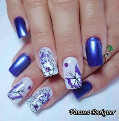 Beautiful looking dark blue nail art design with flowers and butterflies. The nails have blue and white polishes painted on them with the white ones having the flower and butterfly designs on them.