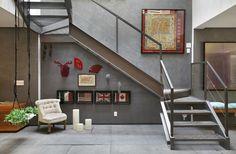 Sala de estar com sofá cinza, quadros de fotografias do fotógrafo Rodrigo Kassab, luminária de piso, e almofadas