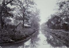 Zicht op een kanaal in het district Commewijne, met bruggetje dat naar enkele huizen leidt. Datum: Locatie: Commewijne, Suriname Vervaardiger: toegeschreven aan Augusta Curiel Inv. Nr.: 74-03 Fotoarchief Stichting Surinaams Museum
