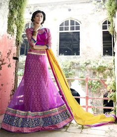 Pink Net Embroiderd Lehenga Choli - https://www.frenzykart.com/wp-content/uploads/2016/07/3559_11007.jpg - Magenta pink shade net A-Line lehenga choli features stick on crystal,stone,resham thread,beads and zari embroidered floral and paisley pattern applique enhanced lehenga. Paisley jacquard floral pattern inner layer adds to the look of the attire. Shiny brocade lace adored floral pattern embroidered hemline frames the look. Comes with matching choli in raw silk and yellow