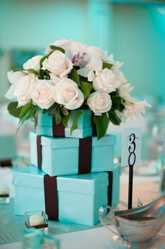 Tiffany Blue and Brown Wedding Centerpieces: Tiffany Blue Boxes with Brown Ribbon topped with White Roses surrounded by white tea light candles. #tiffanybluewedding #weddingcenterpieces