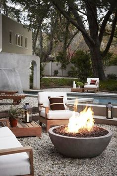 Fire pit in backyard with white and wood patio furniture and swimming pool: