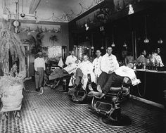 Barber shop, owned and operated by Billy Frantz; located across from old Anaheim City Hall, at 106 West Center Street (later Lincoln Ave.), Anaheim; view shows interior of barber shop with three men in the three barber chairs, three employees, among them Monte Webb and Carl Vanatta, and Lee Baker, the shoe shine man, at far left.