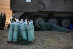 On July 10, 2014 an Israeli soldier sleeps near a mobile artillery unit outside the Gaza strip by Baz Ratner- Reuters.
