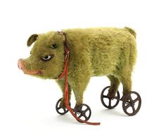 green mohair pig ~ white and black eliptical glass eyes, pink painted carved wooden nose and mouth, oil-cloth collar on cast-iron wheels with mechanism causing a squeak, 1920s -