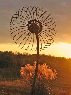 Giant Flower: Support-end loader lift arm, hub-brake drum, petals-bull rake tines, pistol-cultivator parts, seed pod-gas stove burner (height 10', flower width 5')