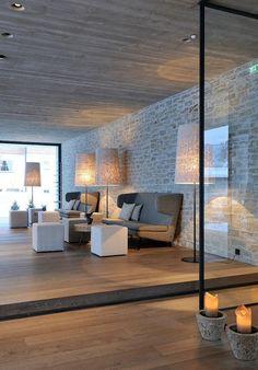 salon superbe et spacieux ave le mur en pierre apparente et le plafond en béton