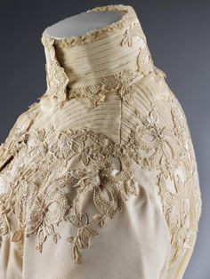 Intricate floral embroidery decorates this weddinng dress with silk bodice and skirt,  designed by Houghton & Dalton, London in 1902.