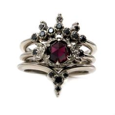 Blood Moon Gothic Engagement Ring Set - Rose Cut Garnet with Black Diamond Side Bands - Triple Moon Goddess I love the unexpected shapes that the wedding bands create centered around a nontraditional 3 stone engagement ring. The engagement ring is a triple moon goddess ring that is set with your choice of a 5 or 6mm rose cut garnet in the center, a 6mm is shown is the photos. The 5mm garnets weigh approximately .50 carats and the 6mm rose cut garnets are approx. .80 carats. Next to the…