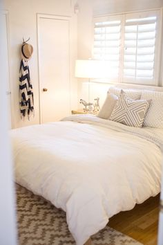 Minimalist bedroom with ivory linen headboard bed and vintage brass trunk nightstand #2