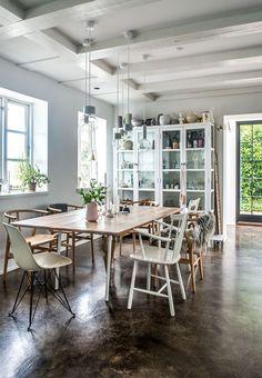 Spiseplads med forskellige stole og gammelt vitrineskab malet hvidt