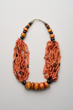 """Moroccan necklace which is made up (""""assembled"""") by using a variety of components - mostly older and recycled.   The materials are branch coral (a copious amount of it and of good quality), amber (or an excellent imitation of it), ebony, silver, amethyst, amazonite, and glass - all of which are very typical. Morocco, Draa Valley, Berber people; probably assembled mid 20th c. Height, as shown: 30.5 cm."""