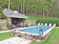 Semi-inground pool surrounded by stone.