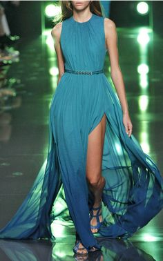 """Titled """"Dive Into the Deep Blue,"""" the Spring 2015 collection reveals an underwater world where evening gowns ripple with cascading pleats and waves of glistening lace. Amidst the stream of flowing dresses lies '70s-inspired sportswear—sheer shirts, silk jumpsuits, and billowing trousers—awash with oceanic hues."""