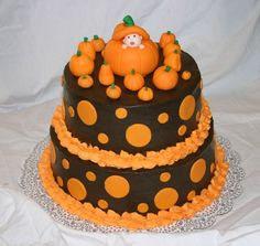 """Halloween Baby Shower Cake - This cake was for a Halloween themed baby shower.  I was at a loss when the request came in and the individual specified for me to """"use my creativity"""".  She only informed me that the napkins she was using were black with orange poka dots!  It was a huge challenge coming up with a design but this is what I came up with.  All fondant decorations.  Baby peeking out of pumpkin has a pacifier in mouth but it's hard to see in this picture.  Chocolate cake with…"""