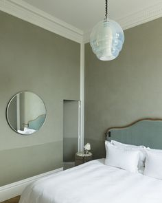 In the bedroom, with walls punctuated by a play of matte-gloss gray-green paint, contemporary reading lights were embedded in a 1900 headboard. The suspension of the is by Carlo Nason. The German mirror of the was flea market Interior Paint Colors, Decor Interior Design, Paris Apartment Interiors, Architecture Parisienne, Half Painted Walls, Narrow Hallway Decorating, Cabinet D Architecture, Lets Stay Home, Decoration Inspiration