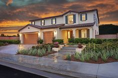 Charming tile steps lead to the generous covered front porch of this Zephyr home in Menifee, CA. The two-story Richmond American plan also features attractive shutters, a Spanish-tile roof and a convenient 3-car garage.