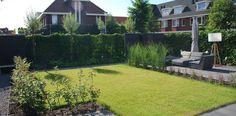 Een moderne, kindvriendelijke tuin met loungegelegenheid.