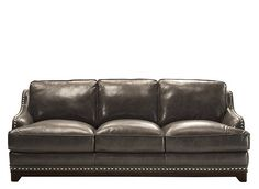 When it comes to making a fashion statement, this Quentin leather sofa's style just doesn't quit. That's because its clever designer blended modern and traditional elements perfectly to create a piece that's equal parts curvy, comfy and luxe. Fans of contemporary furniture will be drawn in by the sleek arms and attractive topstitching, while those who love classic pieces will appreciate the nailhead trim and warm, charcoal gray, semi-aniline leather.