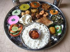"Thali - typical food eaten for lunch or dinner in India. The word ""Thali"" means ""large plate"". It could consist of 4 types of shaak/subji made with potatoes, okra, beans, chickpeas etc, raita - indian yogurt, pickles, lentils, vegetables, paratha (flaked indian bread), Daal (spicy indian lentil soup), a Indian sweet (mithai) and is one of the most healthiest meals"