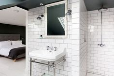 White subway tile in the bathroom open to the bedroom