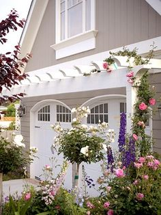 "I've seen this before, and it's been in my ""inspiration files"" for a while...I love the look and softness the arbor and plants bring to the garage doors!"