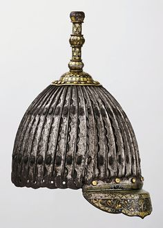 Tibetan, Mongolian, or Chinese multiplate 42 lame helmet, 15th century, this helmet is distinguished by the cusped edge and central ridge of its lames and by the decoration of its plume finial and brim, which are damascened in gold and silver with motifs including a flaming sword of wisdom (center of the brim), and repeating tight concentric spirals. The proportions of the helmet bowl are small enough to suggest that it was made for a child or a very young man. Royal Armouries Museum, Leeds
