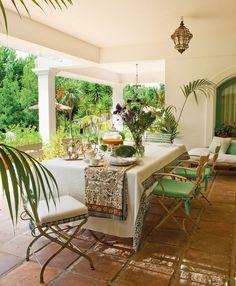 Porche en blanco con comedor de exterior con sillas de hierro_ 00324105