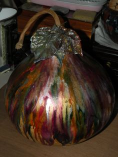 I dripped various colors of alcohol inks on this huge gourde my brother gave me. I also used real leaves from my back yard that I sealed and inked up (the shimmer is gold & silver). I regifted it to him when I was done & he loved it. (by Dorothy)