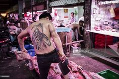 A butcher with a Grim Reaper tattoo holds a knife at a stall at a meat wholesale market in Shanghai, China, on Wednesday, Aug. 17, 2016. Output fell 3.9 percent in the first half of this year and the five provinces hardest hit by flooding produce about one third of the country's pork, according to the National Bureau of Statistics. Photographer: Qilai Shen/Bloomberg via Getty Images